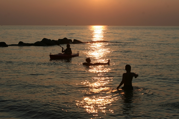 image of people in the lake at sunset