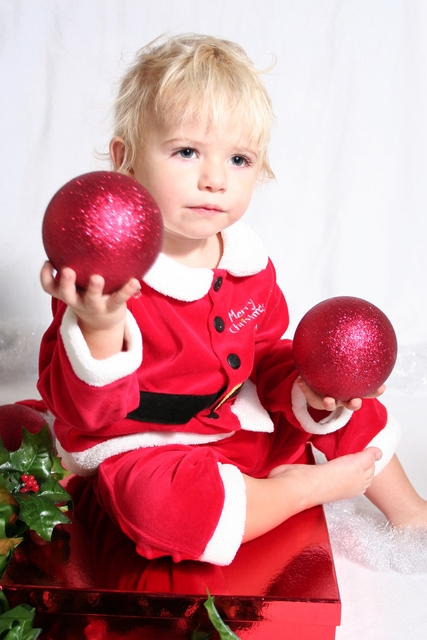 image of a boy holding christmas balls