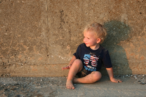 image of a little boy sitting against a block wall