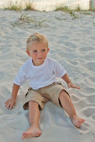 image of child sitting on the beach