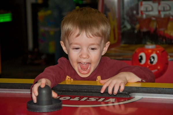 image of boy playing air hockey game