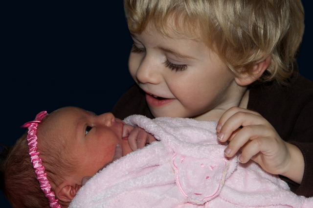 image of a little boy holding his newborn sister
