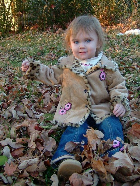 image of child sitting in fall leaves