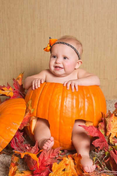 image of a baby sitting in a pumpkin