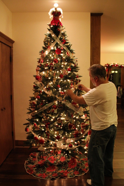 image of man decorating a christmas tree